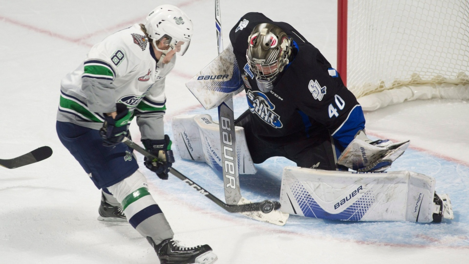 Seattle Thunderbirds centre Scott Eansor tries to put the puck past Saint John Sea Dogs goalie Callum Booth during first period Memorial Cup round robin hockey action in Windsor, Ont. on Tuesday May 23, 2017. (THE CANADIAN PRESS/Adrian Wyld)