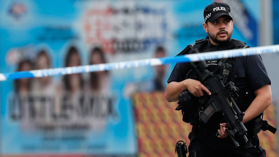Armed police officers patrol a police cordon near the Manchester Arena in Manchester, on May 24, 2017.  (Kirsty Wigglesworth / AP)