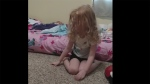 In a video posted to Facebook, Amanda Lewis's daughter Evelyn is seen crying and struggling to stand up, despite encouragement and help from her parents. (Facebook/Amanda Lewis via Storyful)