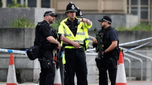 Armed police officers patrol a police cordon near the Manchester Arena in Manchester, Wednesday, May 24, 2017. (AP Photo/Kirsty Wigglesworth)