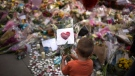 A child places flowers in a square in central Manchester, Britain, Wednesday, May 24, 2017, after the suicide attack at an Ariana Grande concert that left more than 20 people dead and many more injured, as it ended on Monday night at the Manchester Arena. (AP Photo/Emilio Morenatti)