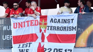 Supporters stay behind a flag outside the stadium prior to the soccer Europa League final between Ajax Amsterdam and Manchester United at the Friends Arena in Stockholm, Sweden, Wednesday, May 24, 2017. (AP Photo/Martin Meissner)