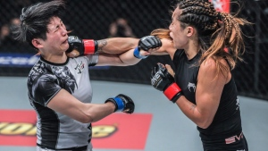 Vancouver-born MMA fighter Angela Lee, right, is shown in this handout image during a third-round stoppage of Jenny Huang on March 11 in Bangkok. (THE CANADIAN PRESS/HO)