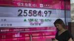 A woman walks past a screen showing the Hang Seng Index at a bank in Hong Kong on Thursday, May 25, 2017. (AP / Kin Cheung)