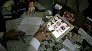 Dr. Anurag Bishnoi, bottom, browses through photographs of his patients on his iPad in his office at the National Fertility and Test Tube Baby Centre in Hisar, India on Dec. 22, 2016. (AP / Altaf Qadri)