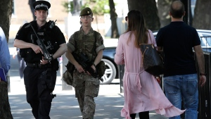 An armed soldier and an armed policeman patrol along Whitehall, in London, Thursday, May 25, 2017. (AP / Kirsty Wigglesworth)