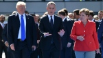 U.S. President Donald Trump, left, NATO Secretary General Jens Stoltenberg and German Chancellor Angela Merkel walk through NATO headquarters at the NATO summit in Brussels on Thursday, May 25, 2017.  (AP Photo/Geert Vanden Wijngaert)