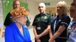 Britain's Queen Elizabeth II, centre, speaks with hospital personnel as she visits the Royal Manchester Children's Hospital to meet victims of the terror attack in the city earlier this week and to thank members of staff who treated them Thursday May 25, 2017. (Peter Byrne/Pool via AP