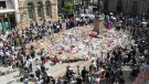 People look at tributes in a square in central Manchester, England, Thursday, May 25, 2017, ahead of a minute's silence for the victims of the suicide attack at an Ariana Grande concert that left more than 20 people dead and many more injured, as it ended on Monday night at the Manchester Arena. (Owen Humphreys/PA via AP)