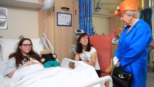 Queen Elizabeth II, right, speaks to Amy Barlow, 12, from Rawtenstall, Lancashire, left, and her mother, Kathy, as she visits the Royal Manchester Children's Hospital in Manchester England, to meet victims of the terror attack in the city earlier this week and to thank members of staff who treated them Thursday May 25, 2017. (Peter Byrne/Pool via AP)