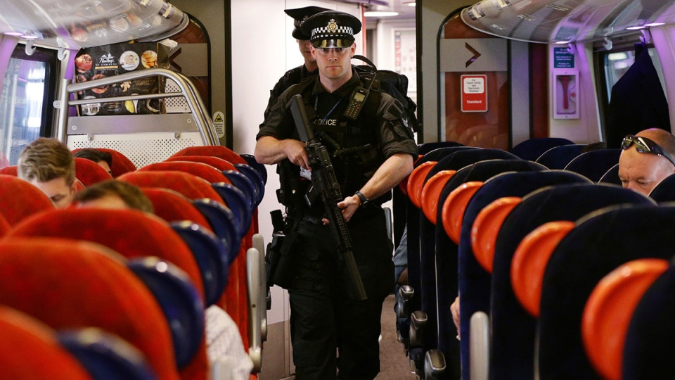 Armed British Transport Police Specialist Operations officers on board a train to Birmingham New Street at Euston station in London as armed police officers are patrolling on board trains nationwide for the first time, Thursday, May 25, 2017. (Yui Mok / PA via AP)