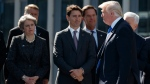 President Donald Trump walks past Canadian Prime Minister Justin Trudeau and British Prime Minister Theresa May after speaking during a ceremony to unveil artifacts from the World Trade Center and Berlin Wall for the new NATO headquarters, Thursday, May 25, 2017, in Brussels. (AP Photo/Evan Vucci)