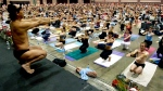Bikram Choudhury, front, founder of the Yoga College of India and creator and producer of Yoga Expo 2003, leads a yoga class at the Expo at the Los Angeles Convention Center on Sept. 27, 2003. A California judge issued an arrest warrant Wednesday, May 24, 2017, for Choudhury, the founder of Bikram yoga, who's been ordered to hand over proceeds from his global fitness business to satisfy a $6.8 million judgment won by a former legal adviser. (AP Photo/Reed Saxon)