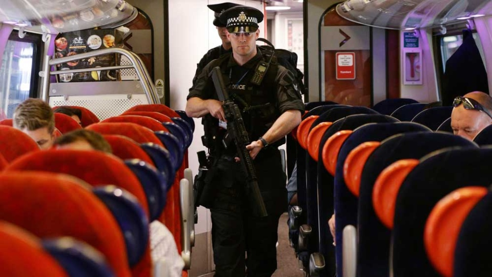 Armed British Transport Police Specialist Operations officers on board a train to Birmingham New Street at Euston station in London as armed police officers are patrolling on board trains nationwide for the first time Thursday May 25, 2017. (Yui Mok/PA via AP)