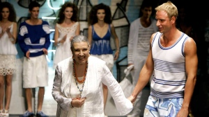 In this June 27, 2006 file photo, Italian designer Laura Biagiotti, left, acknowledges the audience's applause as she holds hands with Italian world swimming champion Massimiliano Rosolino, at the end of her Laura Biagiotti Spring-Summer 2007 men's collection, unveiled during the men's Fashion Week in Milan, Italy. (AP Photo/Antonio Calanni, files)