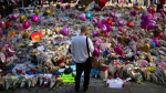 A man stands next to flowers for the victims of Monday's bombing at St. Ann's Square in central Manchester, England, Friday, May 26 2017. British police investigating the Manchester Arena bombing arrested a ninth man while continuing to search addresses associated with the bomber. (AP Photo / Emilio Morenatti)