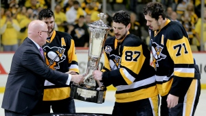 National Hockey League deputy commisioner Bill Daly, left, presents the Prince of Wales Trophy to Pittsburgh Penguins' team captain Sidney Crosby (87) and assistant captains Evgeni Malkin (71) and Chris Kunitz (14) on Thursday, May 25, 2017, in Pittsburgh. . (AP Photo/Keith Srakocic)