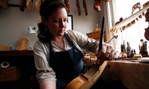 Sonja St. John applies varnish on a violin at her workshop in Neenah, Wis., on Thursday, April 27, 2017. (AP / Carrie Antlfinger)