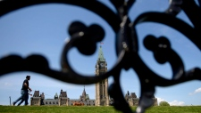 People walk on Parliament Hill in Ottawa on Tuesday, May 23, 2017. THE CANADIAN PRESS/Justin Tang