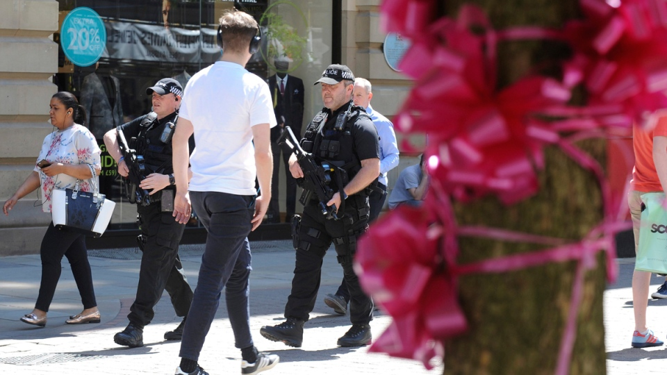 Armed police patrol past tribute pink ribbons on a tree in central Manchester, England, on May 26 2017. (Rui Vieira / AP)