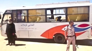 This image released by the Minya governorate media office shows a policeman and a priest next to a bus after stormed the bus in Minya, Egypt, Friday, May 26, 2017. (Minya Governorate Media office via AP)