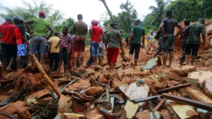 Sri Lankan military rescuers and villagers stand on the debris of a house that was destroyed in a landslide in Bellana village in Kalutara district, Sri Lanka, Friday, May 26, 2017. (AP / Eranga Jayawardena)