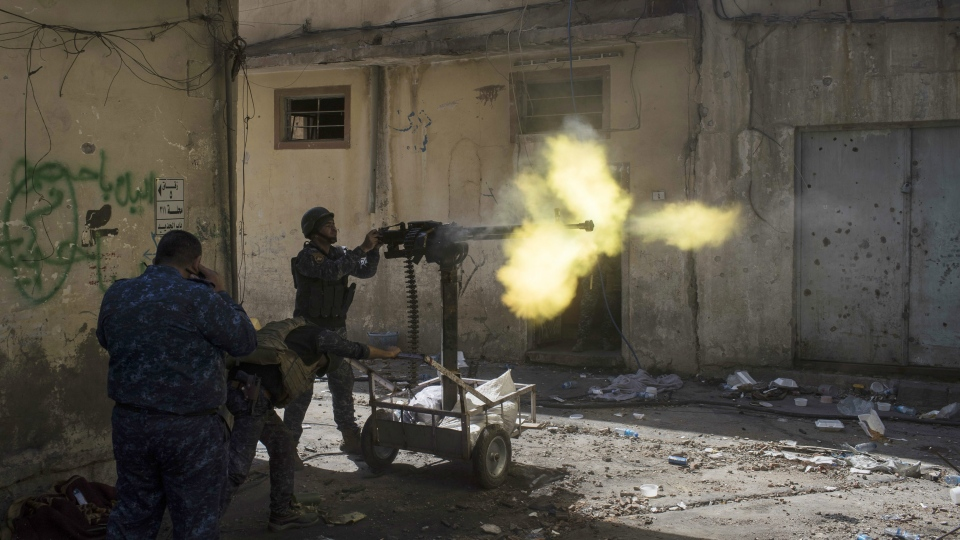 In this March 30, 2017 file photo, federal policemen fire towards Islamic State militant positions in the old city during fighting on the western side of Mosul, Iraq. (AP / Felipe Dana, File)