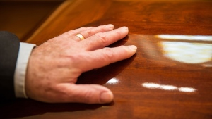 A man places his hand on a casket in this stock photo. (Michelle Gibson/Istock.com)