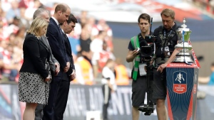 Britain's Prince William, third from left, stands next to wreaths laid on the side of the pitch, as a tribute to the victims of the Manchester bomb attack, before the during the English FA Cup final soccer match between Arsenal and Chelsea at the Wembley stadium in London, Saturday, May 27, 2017. (AP Photo/Matt Dunham)