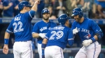 Toronto Blue Jays right fielder Jose Bautista, right, celebrates with second baseman Devon Travis (29) and catcher Luke Maile (22) after hitting a three run home run against the Texas Rangers during fifth inning American League MLB baseball action in Toronto on Saturday, May 27, 2017. (THE CANADIAN PRESS / Chris Young)