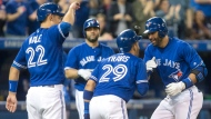 Toronto Blue Jays right fielder Jose Bautista, right, celebrates with second baseman Devon Travis (29) and catcher Luke Maile (22) after hitting a three run home run against the Texas Rangers during fifth inning American League MLB baseball action in Toronto on Saturday, May 27, 2017. THE CANADIAN PRESS/Chris Young