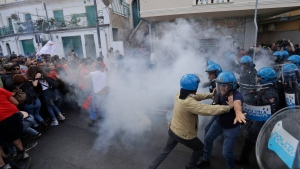 A police officer holds back other policemen as some demonstrators do the same with their side after a contact during an anti-G7 rally near the venue of the G7 summit in the Sicilian town of Taormina, Italy, Saturday, May 27, 2017. (AP Photo/Gregorio Borgia)