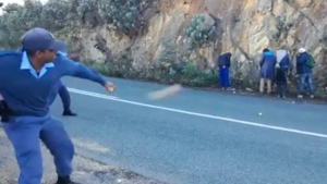 This image from video posted online May 26 appears to show South African police throwing apples at suspects. (Facebook / Kevi van Wyk)