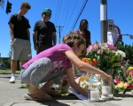 Coco Douglas, 8, leaves a handmade sign and rocks she painted at a memorial in Portland, Ore., on Saturday, May 27, 2017, for two bystanders who were stabbed to death Friday while trying to stop a man who was yelling anti-Muslim slurs and acting aggressively toward two young women. (AP / Gillian Flaccus)