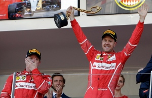 Ferrari driver Sebastian Vettel of Germany celebrates with his teammate Kimi Raikkonen of Finland, left, after winning the Formula One Grand Prix at the Monaco racetrack in Monaco, Sunday, May 28, 2017. (AP / Claude Paris)