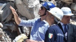 Prime Minister Justin Trudeau, left, takes a tour of Amatrice, the central Italian town brought to rubble by an August earthquake that killed nearly 300 people, Sunday, May 28, 2017. Wearing a blue hard hat, Trudeau was accompanied Sunday by Foreign Minister Angelino Alfano, local officials and firefighters to visit the devastation and learn firsthand about the Aug. 24 quake and subsequent temblors that shook central Italy for months. (Emiliano Grillotti/ANSA via AP)