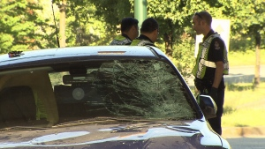 The impact of a collision with several pedestrians near the entrance to Granville Island on Sunday shattered the driver's side of the windshield of a blue Mazda. (CTV)