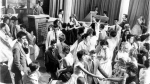In this June 30, 1958, file photo, disc jockey Dick Clark, at podium at upper left, is surrounded by teen-age fans on his nationally televised dance show American Bandstand in Philadelphia. (AP Photo, File)