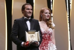 Actor Joaquin Phoenix with his Best Actor award for his role in the film You Were Never Really Here, with jury member and presenter Jessica Chastain poses for photographers during the awards ceremony at the 70th international film festival, Cannes, southern France, Sunday, May 28, 2017. (AP Photo/Alastair Grant)