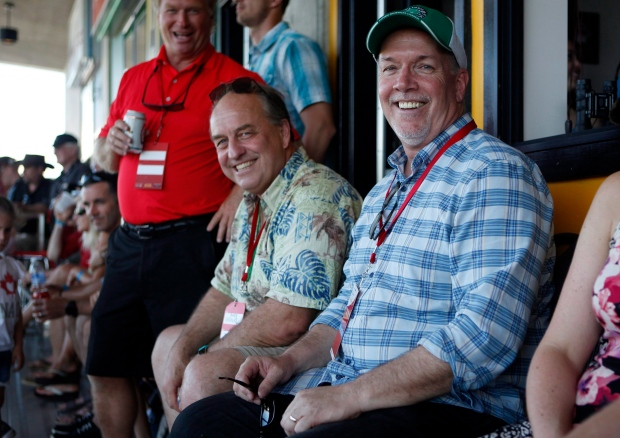 B.C. Green party leader Andrew Weaver and B.C. NDP leader John Horgan take in the final match between Team Canada and New Zealand during cup final action at the HSBC Canada Women's Sevens at Westhills Stadium in Langford, B.C., on Sunday, May 28, 2017. THE CANADIAN PRESS/Chad Hipolito