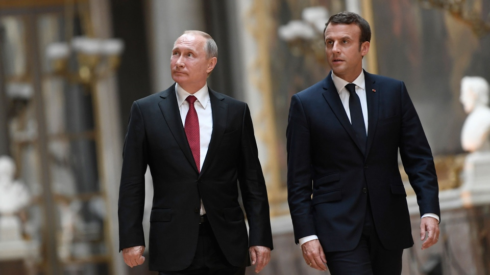 French President Emmanuel Macron, right, and Russian President Vladimir Putin walk in the Galerie des Batailles (Gallery of Battles) at the Versailles Palace as they arrive for a joint press conference following their meeting in Versailles, near Paris, France, Monday, May 29, 2017.  (Stephane de Sakutin/Pool Photo via AP)