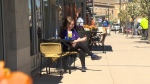A woman sits at a sidewalk patio in Uptown Waterloo. (CTV Kitchener)