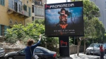A woman waves for taxi, as she stands in front of a digital billboard promoting the 2017 Wonder Woman movie, in Beirut, Lebanon, Tuesday, May 30, 2017. (Hussein Malla/AP)