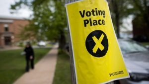 A sign marking a polling station is seen as a pedestrian walks past in Halifax on Nova Scotia's provincial election day on Tuesday, May 30, 2017. (THE CANADIAN PRESS/Darren Calabrese)