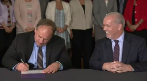 Green Leader Andrew Weaver and NDP Leader John Horgan sign an agreement that would see the NDP form a minority government with the support of the Green party. May 30, 2017. (CTV Vancouver Island)