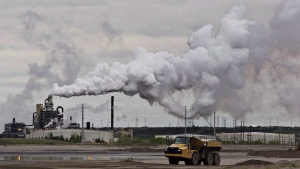 A dump truck works near the Syncrude oil sands extraction facility near the city of Fort McMurray, Alta., on June 1, 2014. (Jason Franson / THE CANADIAN PRESS)