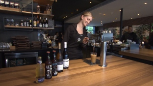 Starbucks store manager Merry Lou Proudfoot pours a beer at the location on Main Street in Mount Pleasant. The location is the in Western Canada to allow the sale of wine, beer and cider. (CTV)