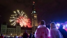 People watch fireworks as they explode behind the Peace Tower during Canada Day celebrations on Parliament Hill, in Ottawa, on Friday, July 1, 2016. (THE CANADIAN PRESS/Justin Tang)