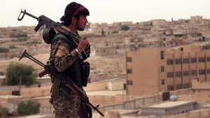 This Sunday, April 30, 2017, file photo, provided by the Syria Democratic Forces (SDF), shows a fighter from the SDF carrying weapons as he looks toward the northern town of Tabqa, Syria. (Syrian Democratic Forces, via AP, File)