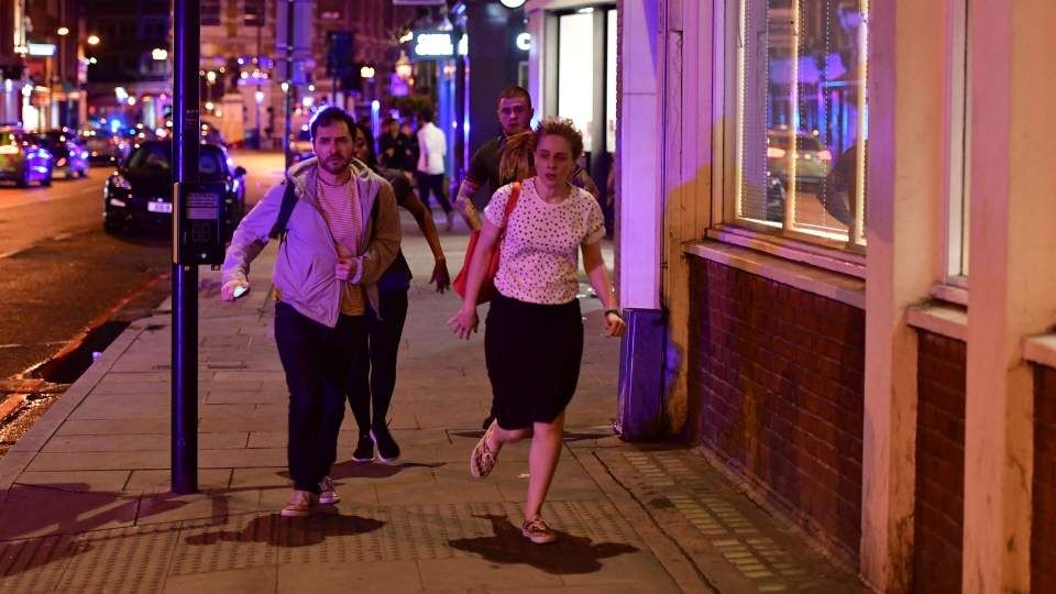 People run down Borough High Street as police are dealing with a 'major incident' at London Bridge in London, Saturday, June 3, 2017. (Dominic Lipinski / PA via AP)